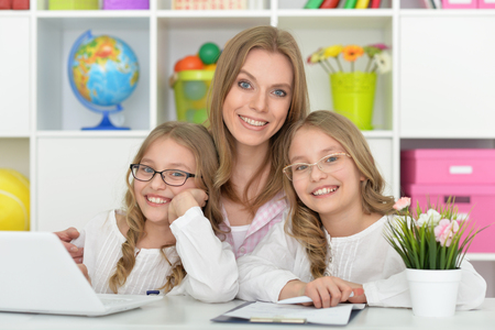 tweens: Mother helping her daughters with homework at home