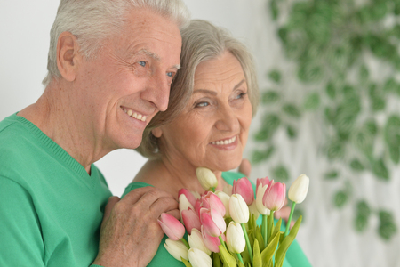 gives: happy senior man gives flowers to a woman Stock Photo