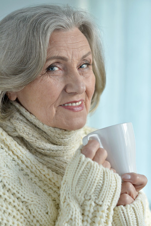 unwholesome: sick senior woman  with cup of tea at home