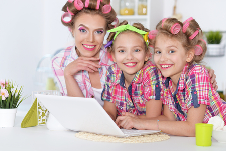 hair curlers: Cute  tweenie girls and mother  in hair curlers  with laptop at home Stock Photo