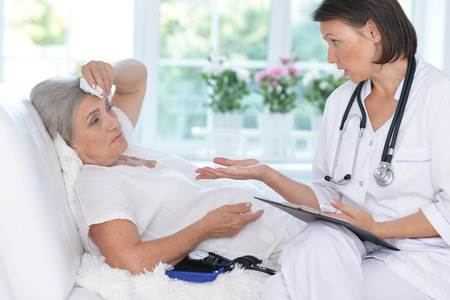 amiable: Senior woman portrait in hospital with caring doctor