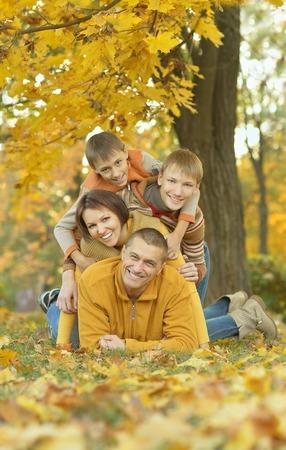 familias unidas: Familia sonriente feliz que se relaja en el bosque de otoño Foto de archivo