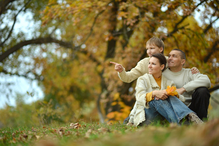 Nice happy family sitting in the autumn park