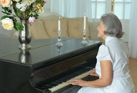 Portrait of happy elderly woman playing the piano at home