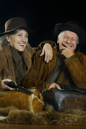 stickup: Two smiling hunters in western clothes, closeup