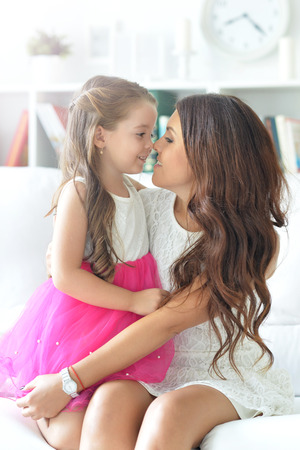 relations: Young mother with her daughter hugging, positive feelings, good relations.