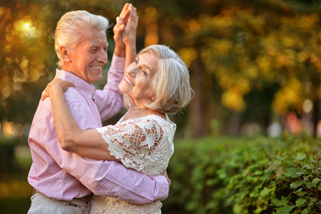 portrait of beautiful caucasian senior couple dancing in the park Stockfoto
