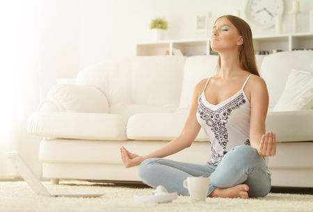 young beautiful woman meditating sitting on the floor at home Foto de archivo