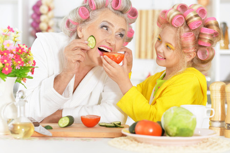 preadolescent: Senior woman and granddaughter at kitchen with  vegetables