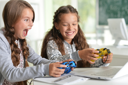 Little twin girls using laptop playing video games Stock Photo