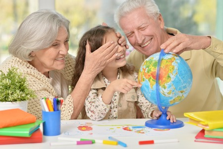 Portrait of a happy grandparents with granddaughter drawing together Stock Photo