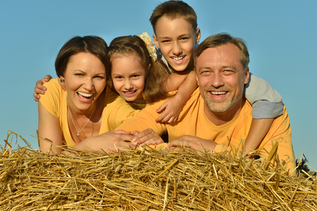 Portrait of a happy family at summer field Stock Photo