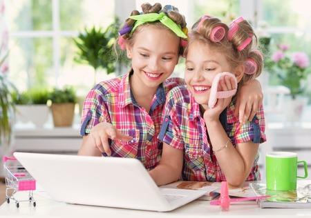 hair curlers: Cute  tweenie girls  in hair curlers  with laptop at home