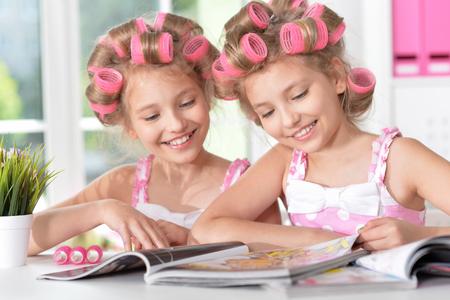 hair curlers: Cute  tweenie girls  in hair curlers  with magazine