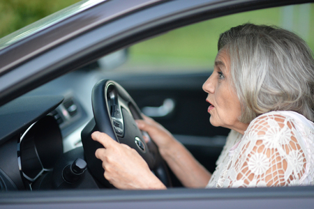 portrait of stressed senior woman driving car Stock Photo