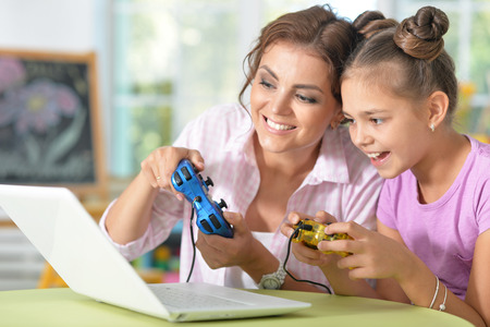 Young mother and her cute daughter playing videogames on laptop at home