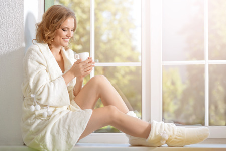 full lenght: full lenght portrait of young beautiful woman with a cup of tea sitting on windowsill