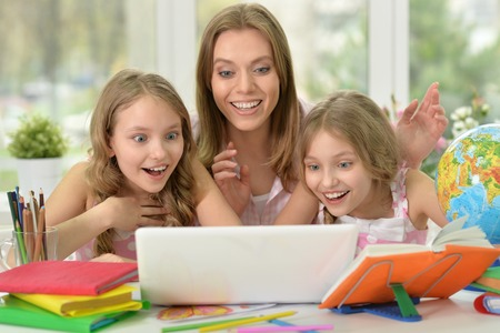 tweens: portrait of Cute girls  with mother on lesson with laptop