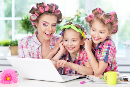 portrait of happy  Mother and little daughters in hair curlers with laptop  at home Stock Photo