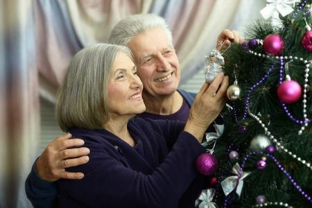 decorating christmas tree: Portrait of happy senior couple decorating Christmas tree