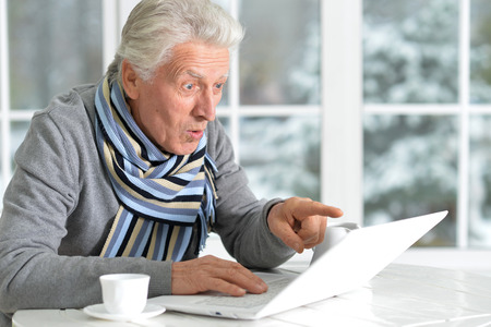 Portrait of exited senior man with laptop Stock Photo