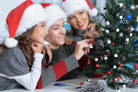 decorating christmas tree: Young mother with her children decorating small Christmas tree Stock Photo