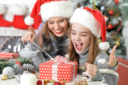 Young beautiful mother helps her daughter to unwrap her Christmas present