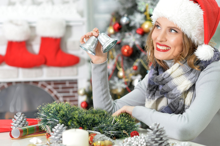 silver bells: Portrait of young beautiful woman in Santa hat holding christmas decoration, silver bells