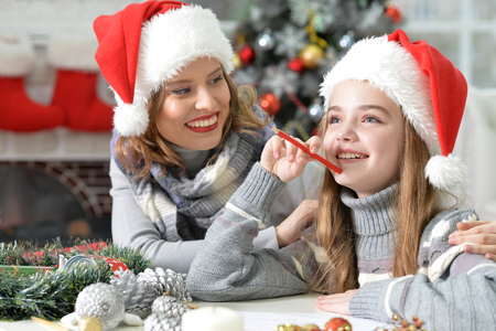helps: Young beautiful mother helps her daughter to write letter to Santa Stock Photo