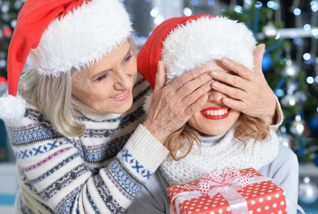 Young and senior women in santa hats having fun together. Senior woman closes eyes of her daughter makes surprise