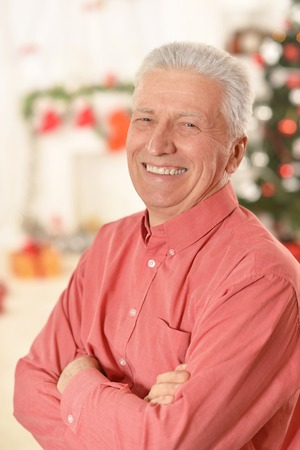 arma: Portrait of smiling senior man standing with arma crossed