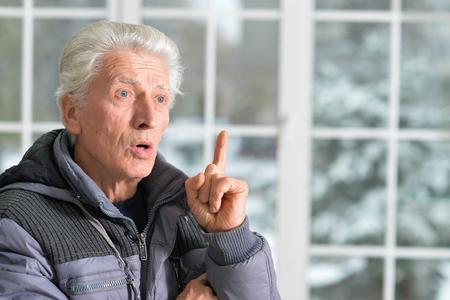 raises: Portrait of senior man has an idea and raises his finger up