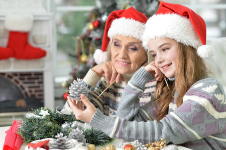 granddaughters: Portrait of senior woman with her cute granddaughters coloring pine cone for decorating Stock Photo