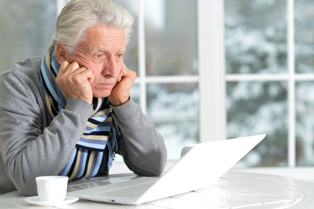Portrait of thoughtful senior man with laptop