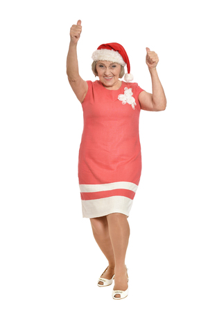 full lenght: Full lenght portrait of happy  senior woman in Santa hat showing thumbs up isolated on white background