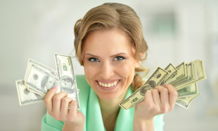 Portrait of smiling young businesswoman holding dollar banknotes looking at camera