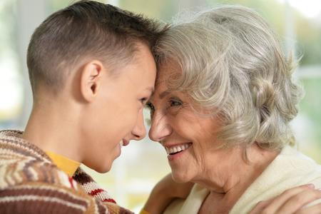 Retrato de abuela feliz y su nieto adolescente miran el uno al otro