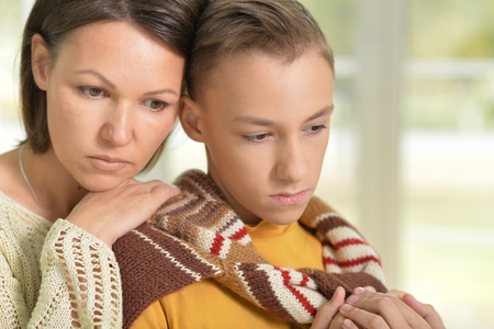 lamentable: Portrait of serious mother and son looking at the distance