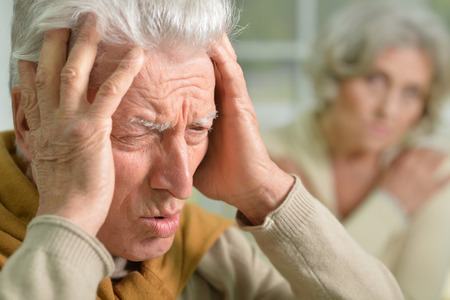 Portrait of shocked senior man with hands on his head