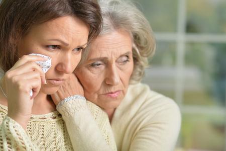 mamma: Portrait of sad senior and young women Stock Photo