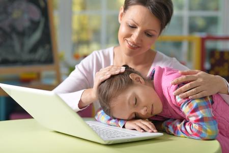ner: Tired little girl fell asleep on her hands near the laptop, her mother seats ner her