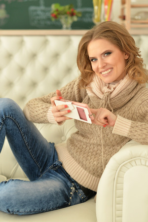 Portrait of young woman with smartphone sitting on sofa