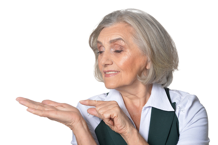 Portrait of senior woman pointing at something on her palm isolated on white background Stock Photo