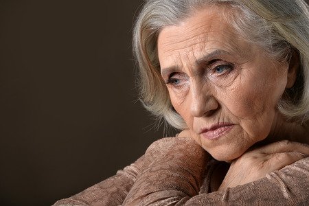 Portrait of senior thoughtful woman  against grey background