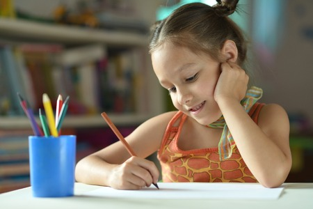 innocent: Portrait of Little girl drawing at home