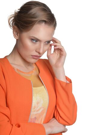 Portrait of thoughtful young woman in orange jacket isolated on white background
