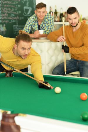 pool halls: Portrait of three young handsome men play billiard Stock Photo