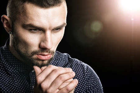 potrait: Potrait of handsome thoughtful young man on dark background Stock Photo