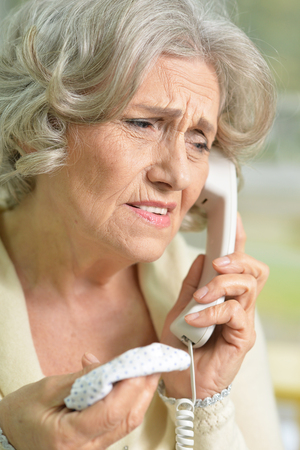 concern: Portrait of upset senior woman holding handkerchief  talking on the phone
