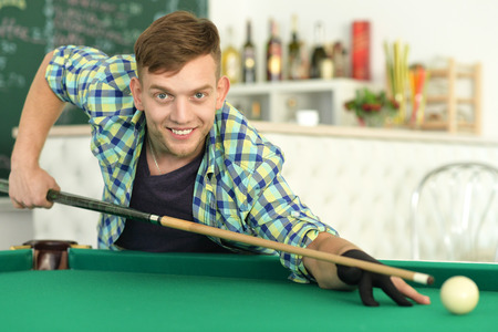 Young handsome man playing billiards in billiard club Stock Photo